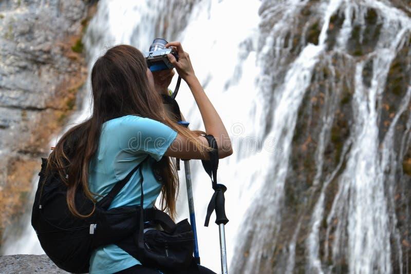 Vrouw met rugzak die foto van waterval nemen royalty-vrije stock afbeelding