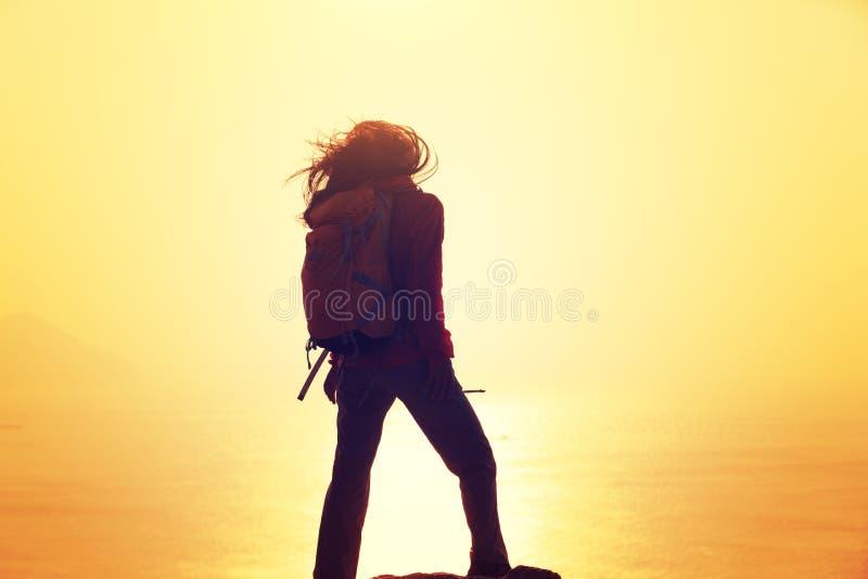 Vrouw met rugzak die zich op zonsopgang winderige kust bevinden royalty-vrije stock foto