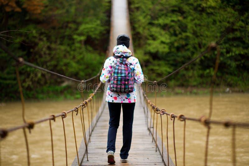 Vrouw met rugzak van het het avonturenconcept van de wandelingslevensstijl de bos en dwarsrivier in bos actieve vakanties stock afbeeldingen