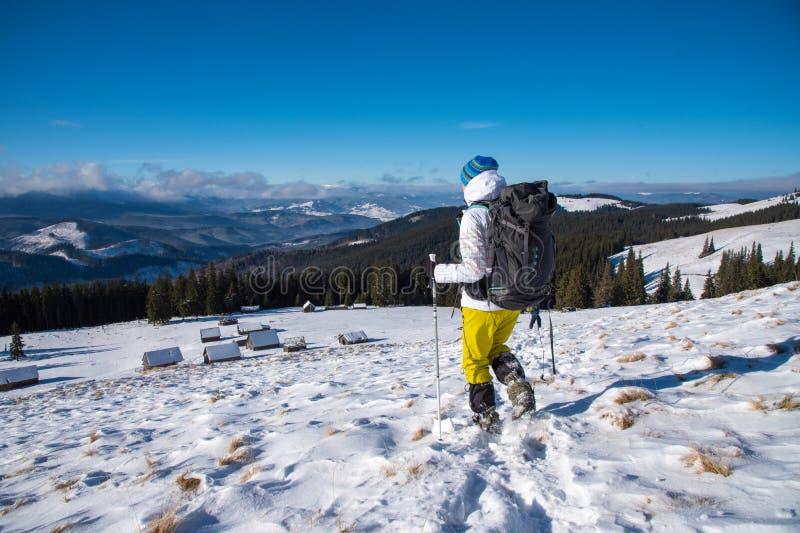 Vrouw met rugzaktrekking in de winterbergen stock afbeeldingen