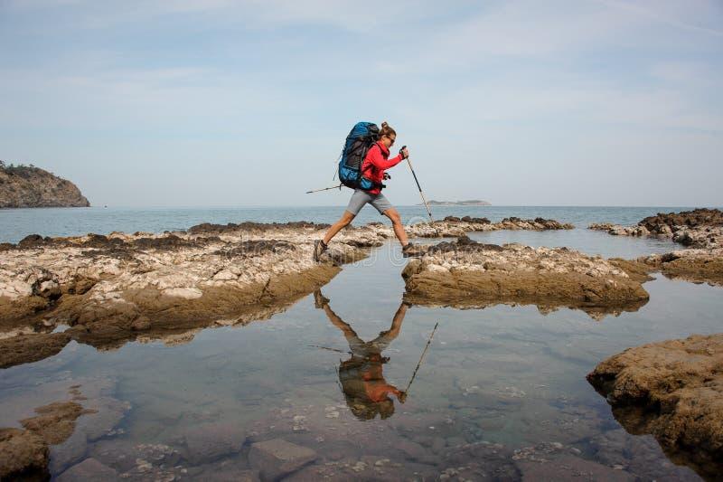 Vrouw met rugzaktreks op een overzeese kust stock foto
