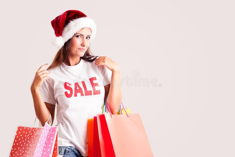 Vrouw met santa hoed en het winkelen zakken stock foto's