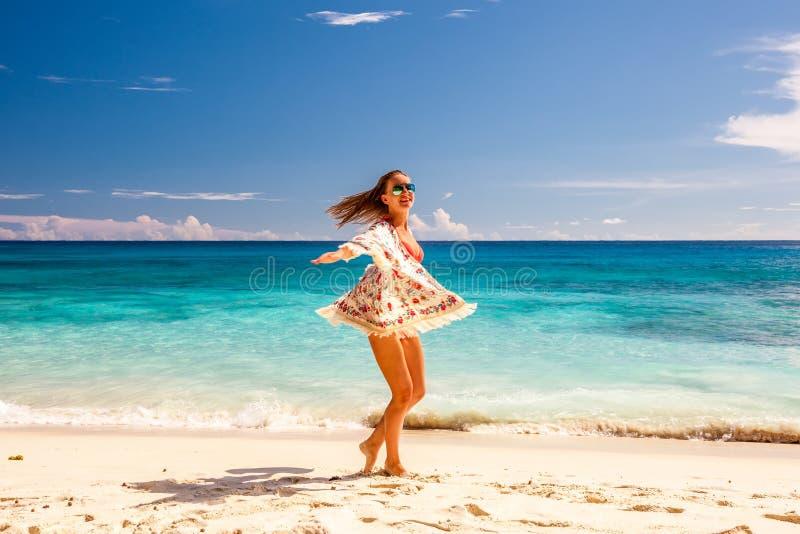 Vrouw met sarongen op strand in Seychellen stock foto