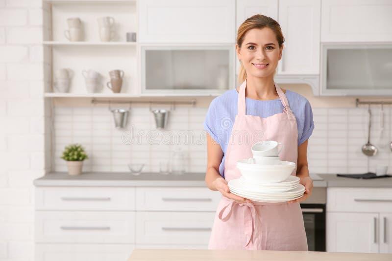 Vrouw met schone schotels en koppen in keuken stock foto's