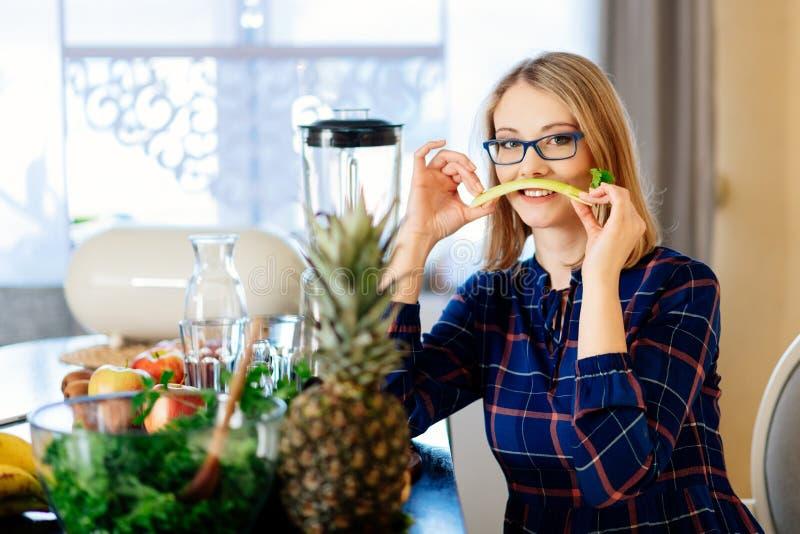 Vrouw met selderie in de keuken stock foto