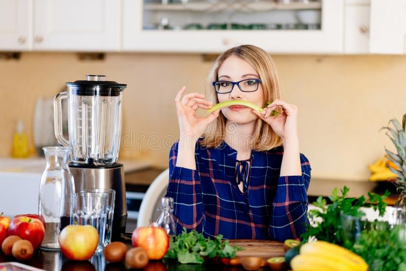 Vrouw met selderie in de keuken royalty-vrije stock afbeeldingen