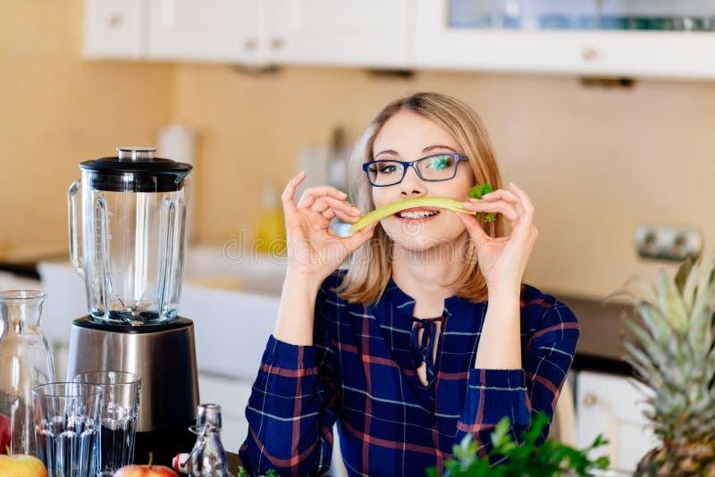 Vrouw met selderie in de keuken stock foto's