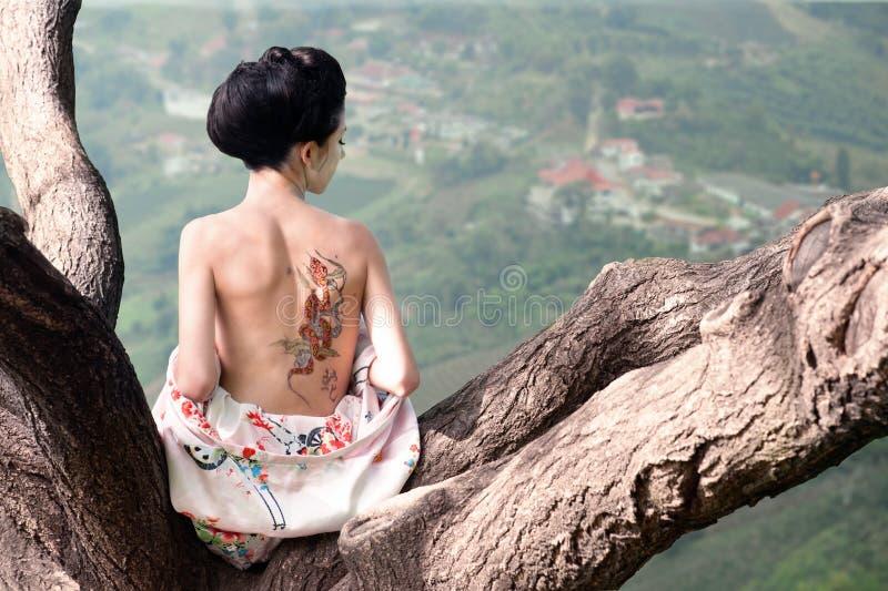 Vrouw met slangtatoegering op achter haar, origineel stock foto