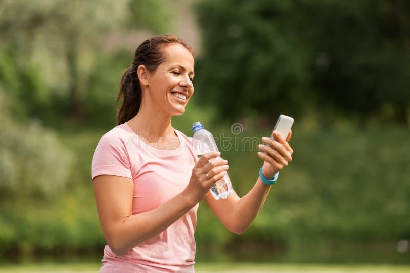 Vrouw met smartphone drinkwater in park stock afbeelding