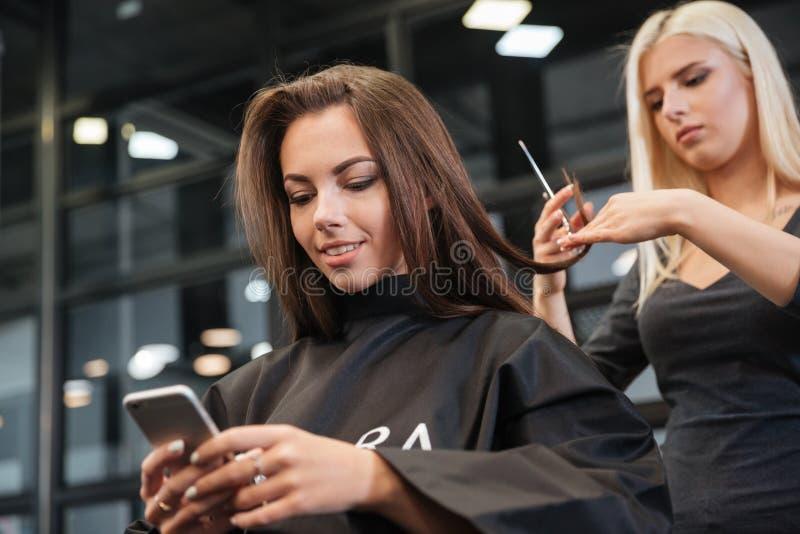 Vrouw met smartphone en kapper die haar het stileren maken bij salon royalty-vrije stock afbeeldingen