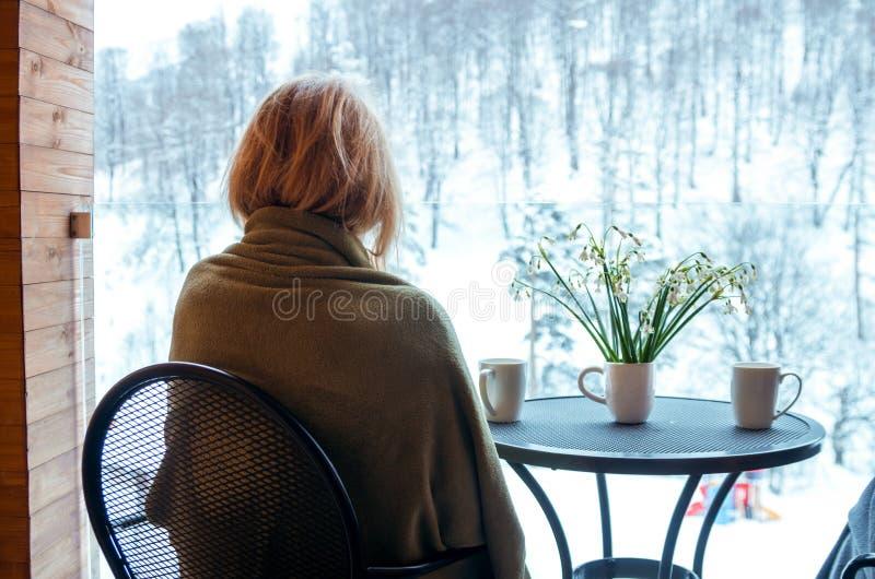 Vrouw met sneeuwklokjes en drankmokken op balkon, de Wintertijd stock foto's