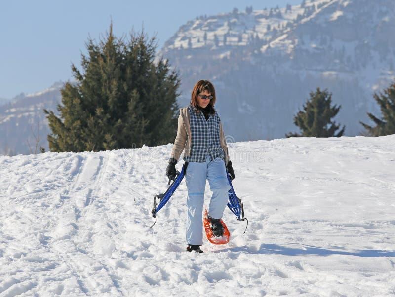 Vrouw met sneeuwschoenen in de winter stock foto's