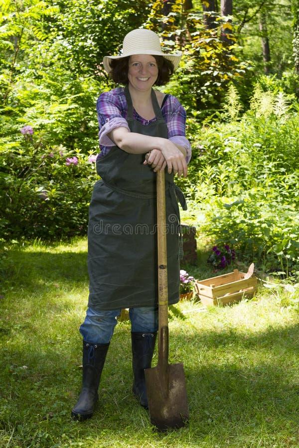 Vrouw met spade in een tuin stock fotografie