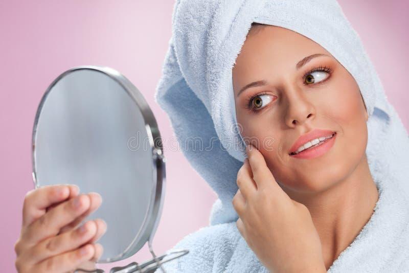 Vrouw met spiegel het in hand kijken zelf stock foto's