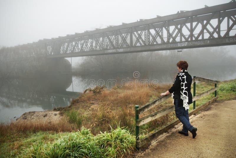 Vrouw met spoorwegbrug en mist stock afbeelding