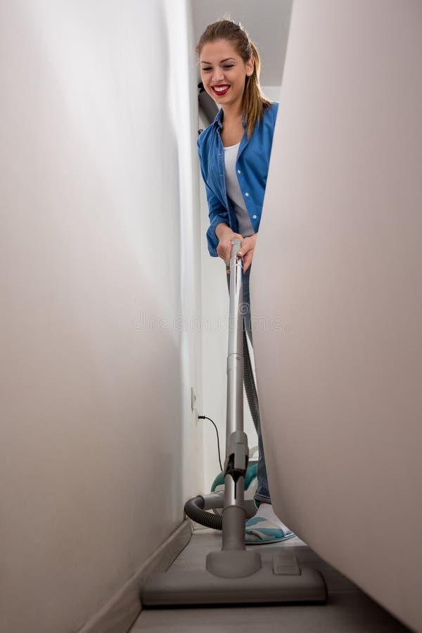 Vrouw met stofzuiger schoonmakend tapijt stock foto