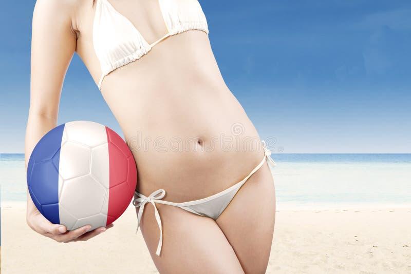 Vrouw met swimwear en voetbalbal stock afbeelding