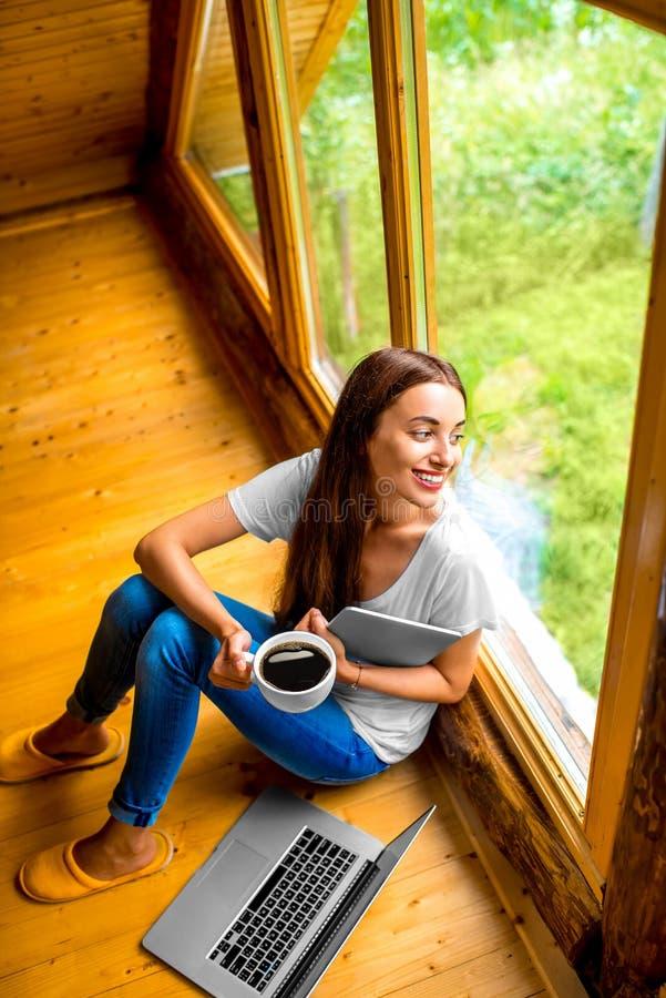 Vrouw met tablet dichtbij het venster in plattelandshuisje royalty-vrije stock foto