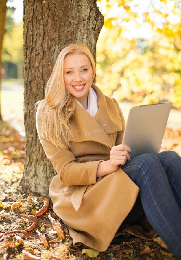 Vrouw met tabletpc in de herfstpark royalty-vrije stock afbeelding
