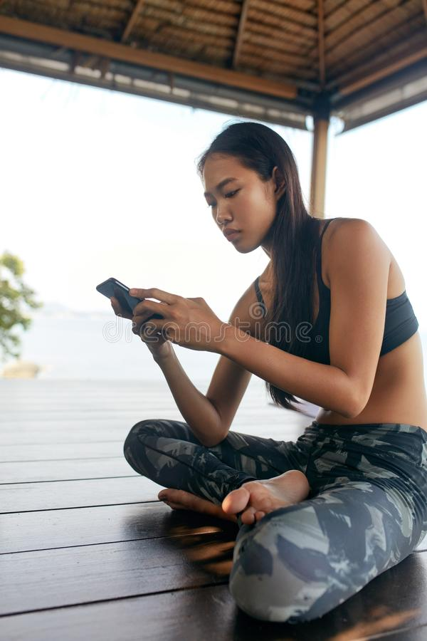 vrouw met telefoon Aziatisch Meisje in Sportkleren die Smartphone gebruiken royalty-vrije stock foto