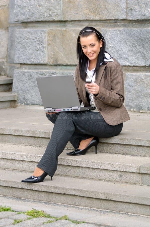 Vrouw met telefoon en laptop stock fotografie