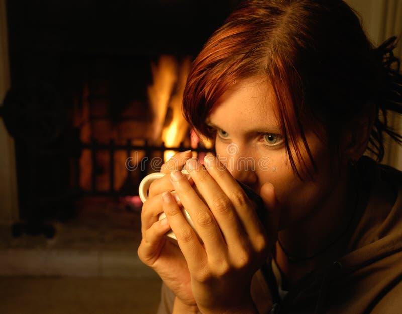 Vrouw met thee (schoorsteen erachter) royalty-vrije stock fotografie