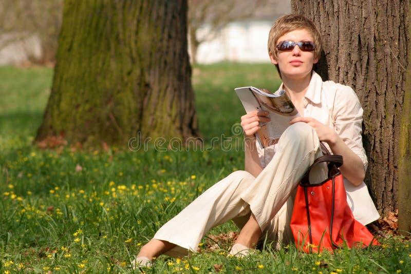 vrouw met tijdschrift in het park stock fotografie