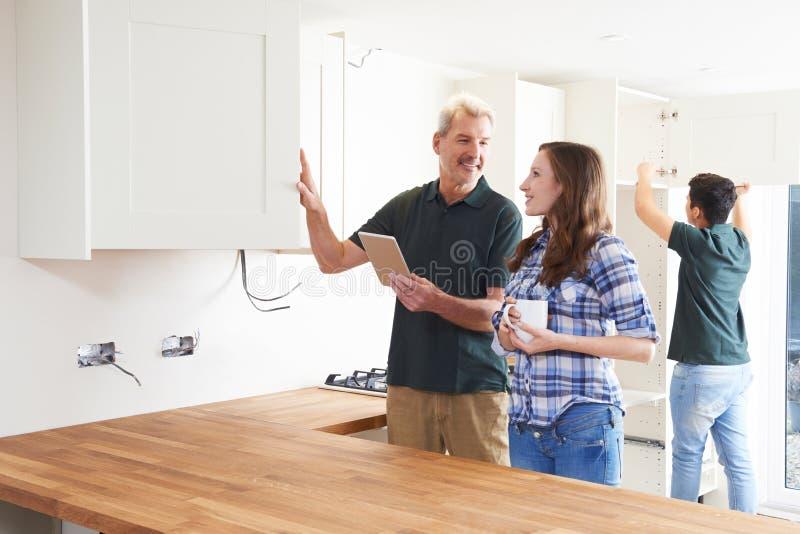Vrouw met Timmerman Looking At Plans voor Keuken op Digitaal Lusje royalty-vrije stock afbeeldingen