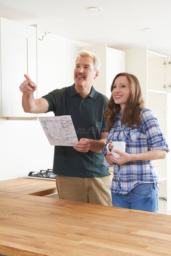 Vrouw met Timmerman Looking At Plans voor Nieuwe Keuken stock foto