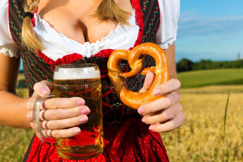 Vrouw met tracht, bier en pretzel in Beieren stock afbeelding