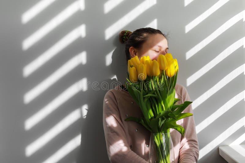 Vrouw met tulpen Jong wijfje met gele natuurlijke het portretlevensstijl van de bloementulp dichtbij witte achtergrond royalty-vrije stock foto's