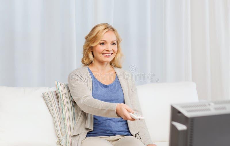 Vrouw met TV van de afstandsbedieningomschakeling thuis stock fotografie
