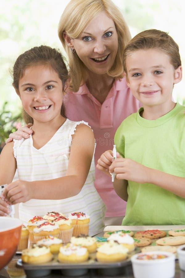 Vrouw met twee kinderen die koekjes verfraaien stock afbeelding