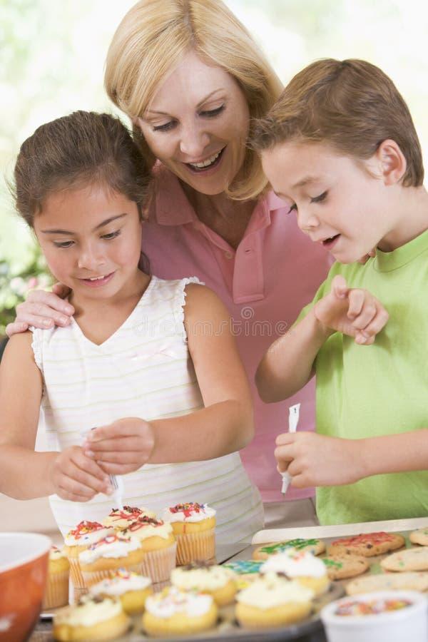 Vrouw met twee kinderen die kok verfraaien royalty-vrije stock afbeelding