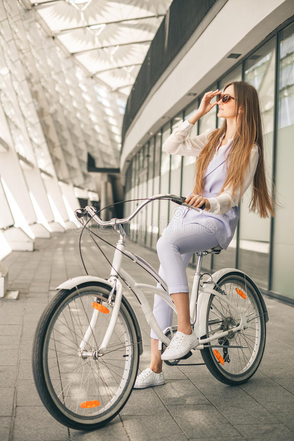 Vrouw met uitstekende fiets Zijaanzicht van vrolijke jonge vrouw in zonnebril royalty-vrije stock fotografie