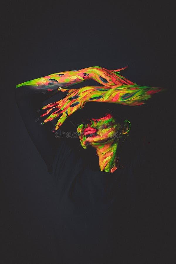 Vrouw met ultraviolette verf op gezicht stock foto's