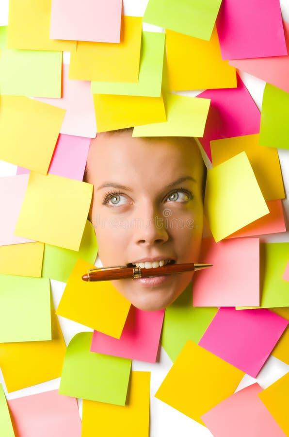 Vrouw met vele herinneringsnota's en pen stock afbeelding