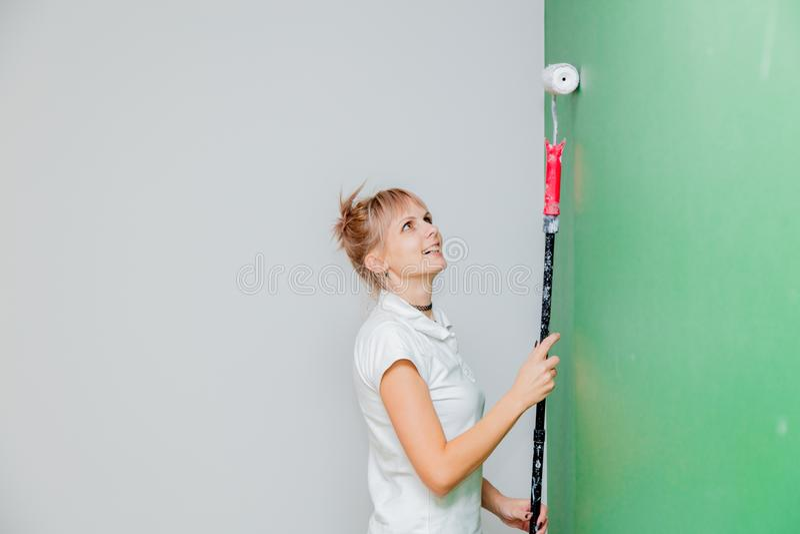 Vrouw met verfrol in eigen huis stock fotografie