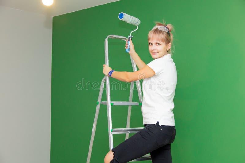 Vrouw met verfrol en ladder in eigen huis stock foto's