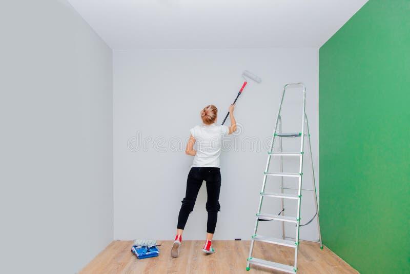 Vrouw met verfrol en ladder in eigen huis royalty-vrije stock afbeeldingen