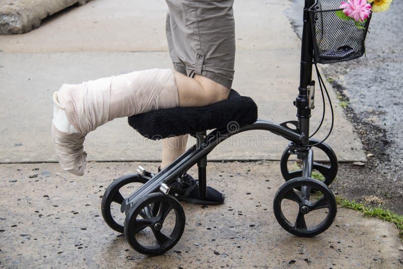 Vrouw met verpakt been op de bestuurbare autoped van de knieleurder met bloemen op mand en mobiele telefoon binnen op ruw gebroke royalty-vrije stock fotografie