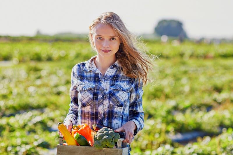 Vrouw met verse organische groenten van landbouwbedrijf stock foto's
