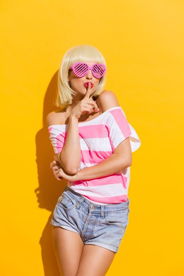 Vrouw met vinger op haar lippen stock foto's