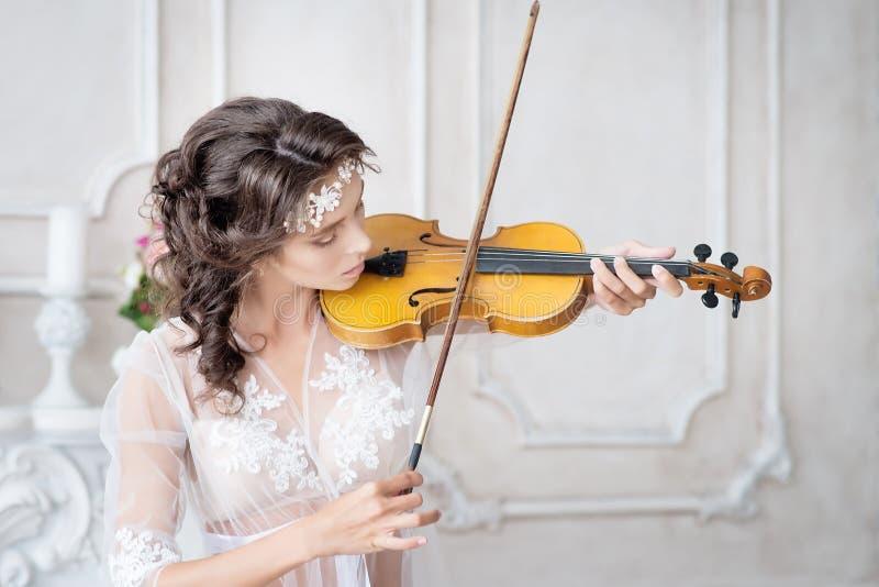Vrouw met viool in witte peignoir boudoir verleidelijk stock fotografie