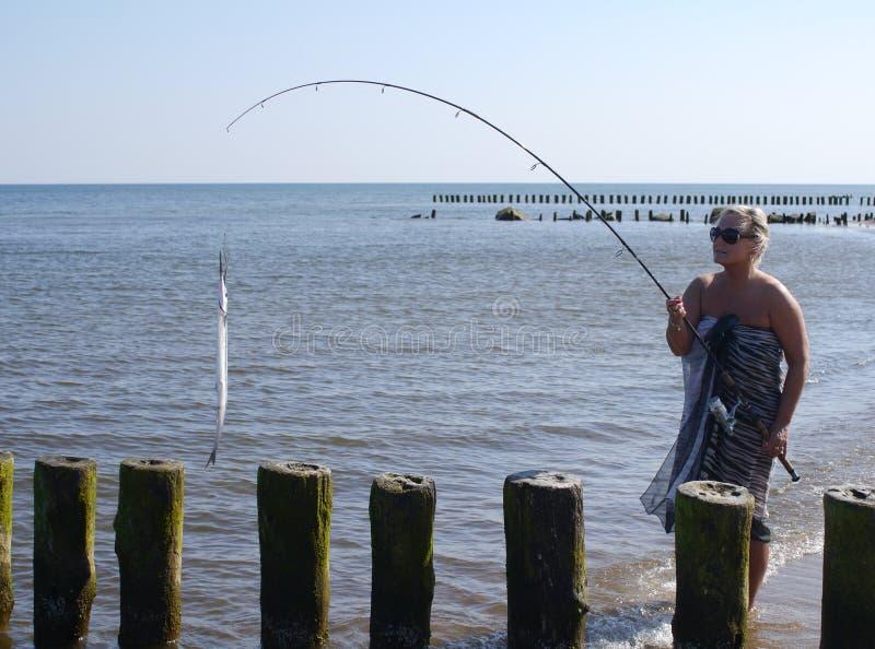 Vrouw met vissen en hengel stock afbeelding