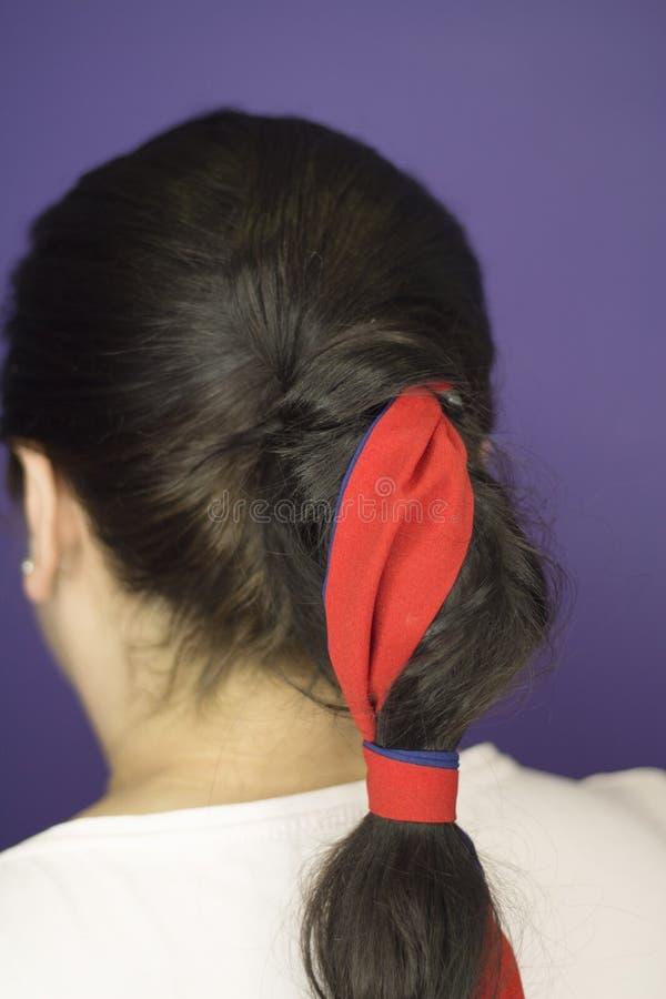 Vrouw met vlecht met een rode boog wordt verfraaid die stock fotografie