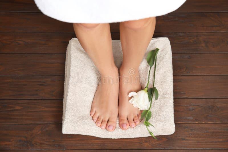 Vrouw met vlotte voeten, bloem en handdoek die zich op houten vloer, hoogste mening bevinden Kuuroord stock afbeeldingen