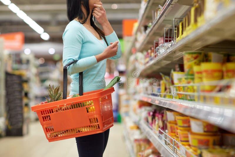 Vrouw met voedselmand bij kruidenierswinkel of supermarkt stock fotografie
