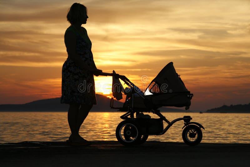 Vrouw met wandelwagen bij zonsondergang royalty-vrije stock afbeelding