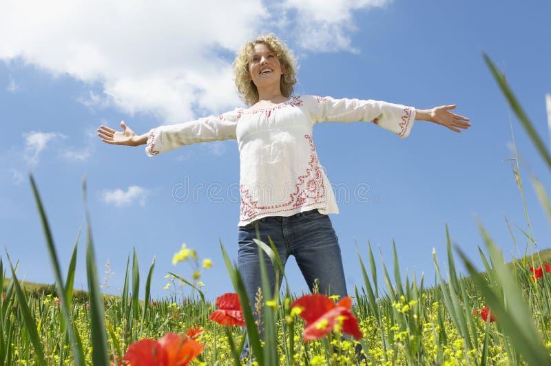 Vrouw met Wapens Uitgestrekte Status in Poppy Field stock foto